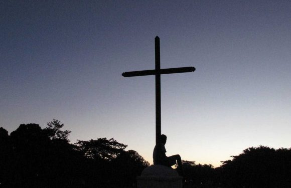 Cross with a person sitting at the foot of the cross