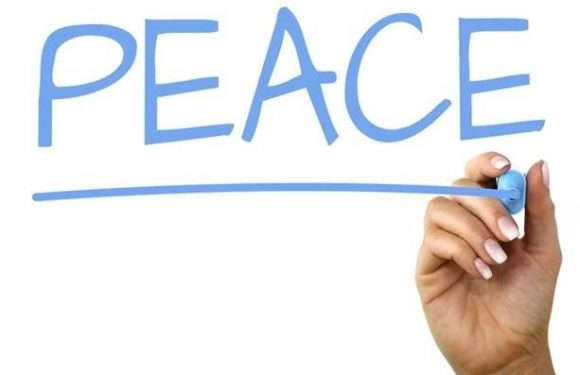 hand writing the word peace