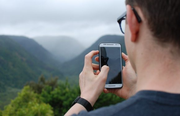 Person taking picture of mountains with cell phone